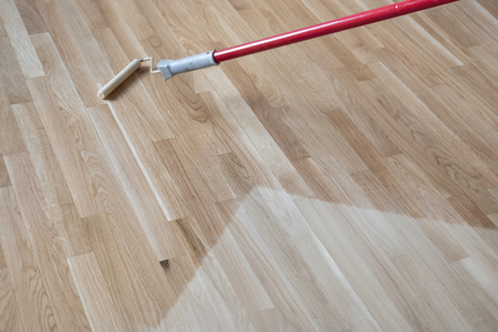 lacquering Varnishing a polished oak parquet floor by paint roller first layer.  Stockfoto