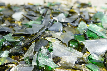 Fragments of colored broken glass on a concrete surface Stock Photo