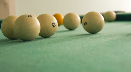 Russian billiards white balls, yellow cue ball, wooden cue on a large table with green cloth Stock Photo