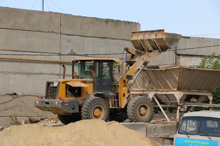 heavy industry: Yoshkar-Ola, RUSSIA AUGUST 25, 2017: Outdoor street concrete plant The excavator loads crushed stone and sand for mixing concrete Editorial