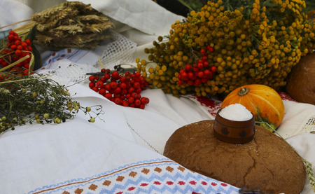 Autumn still life - loaf, pumpkin, mountain ash, tansy, wheat ears, salt, on a white tablecloth with lace Stock Photo