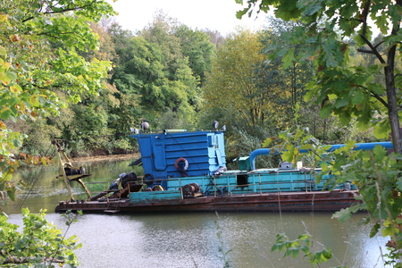 the dredger deepens the river bed in the mainstream Stock Photo