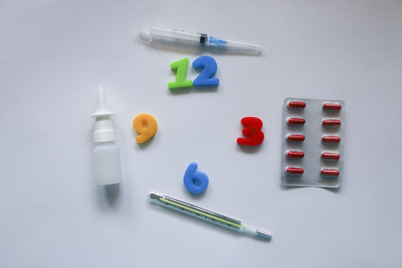 Pills, syringe, inhaler, thermometer, spray and colored numbers symbolizing the clock on a white background Stock Photo