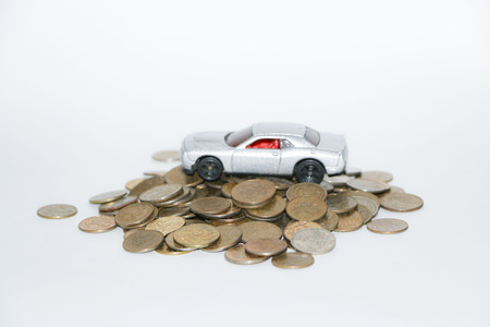 silvery toy car on silvery and golden coins isolated on white background
