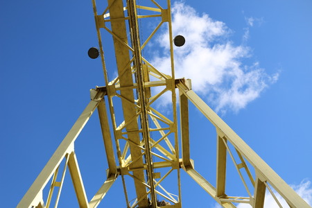 A large gantry crane made of metal colored yellow in the background of a bright blue sky with clouds close-ups moves the cargo