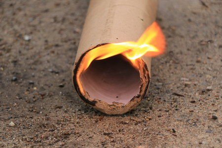 piece of paper tube from pressed cardboard burns on the ground