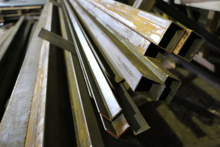 a bundle of long steel square pipes of black metal with a small rust