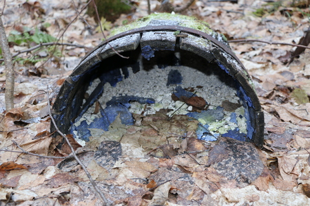 old abandoned wooden barrel with iron rims, broken and rotten, lies in the autumn forest on dry leaves