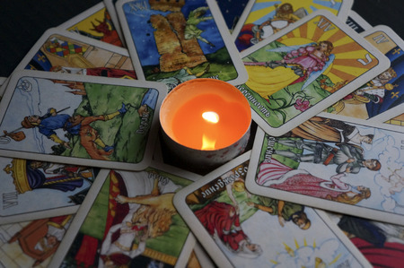 YOSHKAR-OLA, RUSSIA - NOVEMBER 13, 2017: Fortune telling on Tarot cards on a black background with a burning candle Redakční