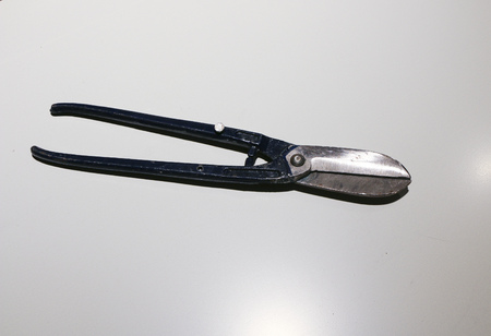 tin snips isolated on white background with iron blue handles and glittering steel blades Stock Photo
