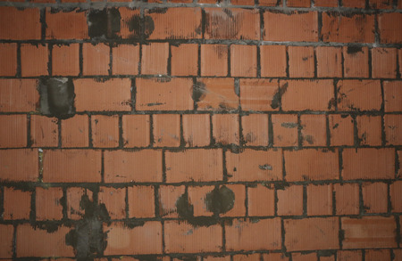 wall of red finishing bricks. sloppy brickwork with blobs of mortar on bricks, uneven rows of bricks, a poor-quality new wall of a residential building.