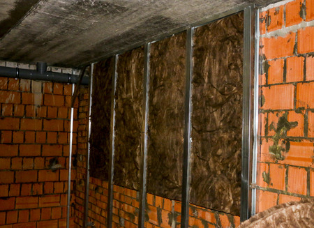 insulation of brick walls in the attic and chimneys. steel carcass of their profile for the insulation of walls, installation of insulation material.