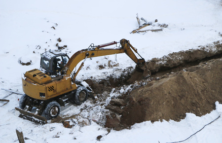 Excavator digs frozen land covered with snowdrifts. preparation of the site for winter construction.   excavator dig  deep trench for padding foundation in winter Stock Photo