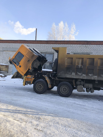 A large career dirty truck got up for winter repairs on the street. The cabin  dump truck is pushed forward to repair the engine.
