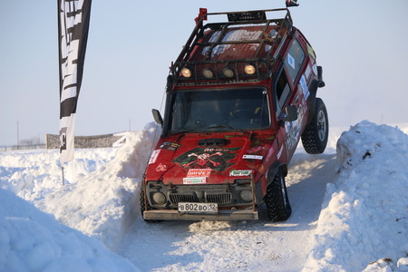 SALTAC-KOREM, RUSSIA-FEBRUARY 11, 2018: Winter auto show jeeps - Ice kneading 2018. driving modified jeep off-road - monster truck rides through snow and snowdrifts, jumping  car from snowy slopes