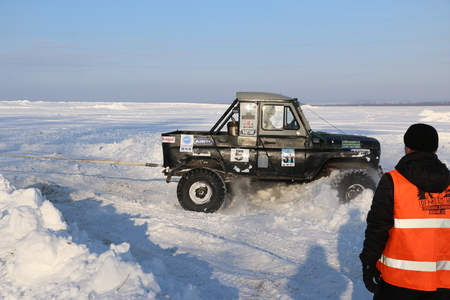 SALTAC-KOREM, RUSSIA - FEBRUARY 11, 2018: Winter auto show jeeps - Ice kneading 2018. driving modified jeep off-road - monster truck rides through snow and snowdrifts, jumping  car from snowy slopes Editorial