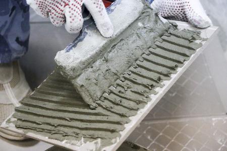 Repair - interior decoration. Laying of floor ceramic tiles. Men's hands tiler in gloves with,  spatula spread  cement mortar on  ceramic floor tile.