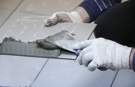 Repair - interior decoration. Laying of floor ceramic tiles. Men's hands tiler in gloves with,  spatula spread  cement mortar on  ceramic floor tile.