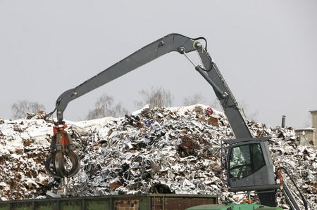 hydraulic grab cleans and tampens  metal debris.  excavator lifts and throws  load with  pneumatic paw with claws.