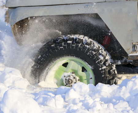 wheel of  car is stuck in snow. spray of snow from  rotating wheel of winter tires. slipping machine in  snow.  machine is in captivity of snowdrift after  snowfall.