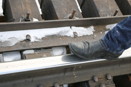 men's legs in jeans and boots are  railway. Walk on  rails. Concept: loneliness, travel,  road of life,  dangerous path. Фото со стока
