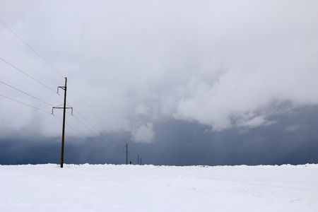 snow field.  plain  covered with white snow under  blue sky with thick white clouds. before  snowfall,  storm,  snowstorm. premonition of  blizzard. in anticipation of  blizzard. Stock fotó