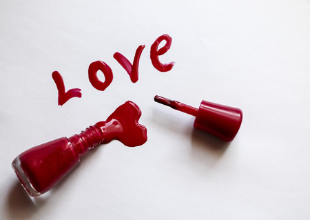 red lacquer. Love - written in red nail polish on  white background. Billet for  postcard - lacomanyak holiday