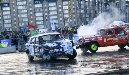 KAZAN, RUSSIA - APRIL 29, 2018: Extreme auto show - car revolt. Cars and drivers in  small arena compete in derby with  demolition. Fighting cars for survival after severe collisions and acciden Редакционное