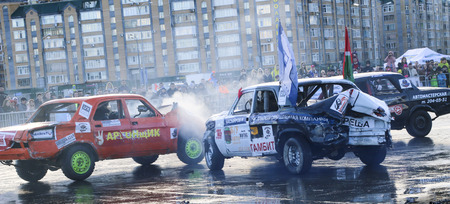 KAZAN, RUSSIA - APRIL 29, 2018: Extreme auto show - car revolt. Cars and drivers in  small arena compete in derby with  demolition. Fighting cars for survival after severe collisions and acciden Editorial