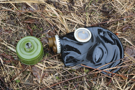 old gas mask lies on  wilted grass after rain. concept: biological and gas danger,  end of  world, Apocalypse, death, war.