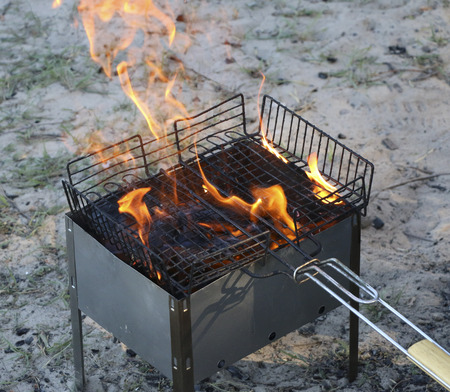 burning grill. on brazier with hot coals lies grill. Black charcoal, brushwood and pine cones are burning and smoldering Stock Photo