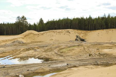 Bagger im Sandsteinbruch Big Orange Digger im offenen Sandbergwerk wartet auf neue Schicht.