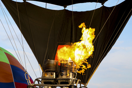 Hot air balloon being inflated for flight. Gas burner fills canopy of balloon with hot air. Pumping fire to apply hot air into fireproof air-balloon. Hot air balloon burner heating air with fire.