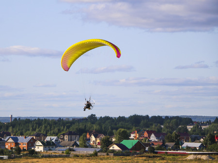 Flight of  motor paraplan.   man flies on  bright colorful motoparaplane above the village, field and construction site. Stock Photo