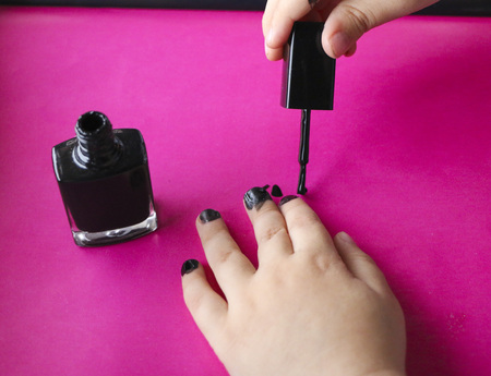 children's manicure. Children's hands paint their nails with black nail polish.  black manicure on childish nails. Stockfoto - 109577108