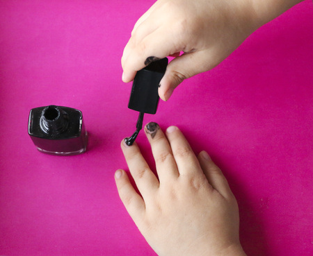 childrens manicure. Childrens hands paint their nails with black nail polish.  black manicure on childish nails. Stockfoto
