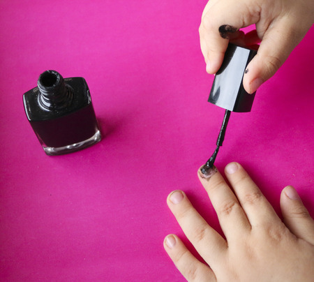 children's manicure. Children's hands paint their nails with black nail polish.  black manicure on childish nails.