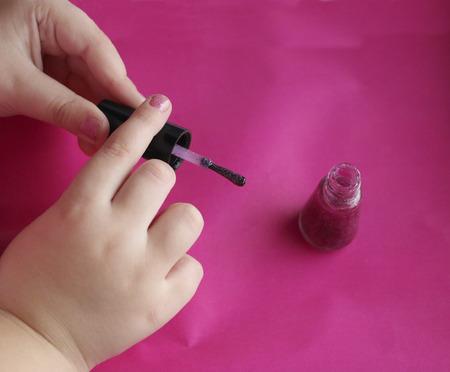 manicure voor kinderen. kinderhanden lakken hun nagels met roze glanzende nagellak. glamoureuze roze manicure op kinderachtige nagels met glitters en strass steentjes. Stockfoto