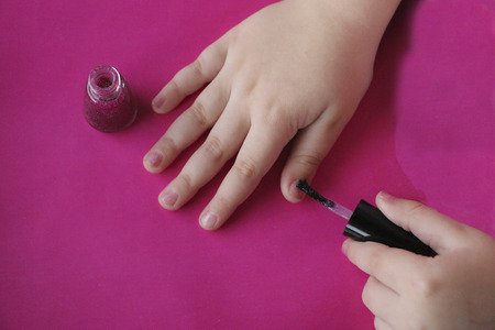 children's manicure. children's hands paint their nails with pink shiny nail polish.  glamorous pink manicure on childish nails with sparkles and rhinestones. Stockfoto - 109577127