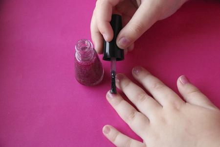 manicure voor kinderen. kinderhanden lakken hun nagels met roze glanzende nagellak. glamoureuze roze manicure op kinderachtige nagels met glitters en strass steentjes.