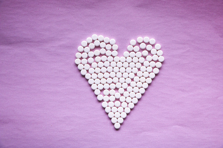 white pills laid out in  shape of  heart on  pink background. concept - heart disease, heart disorders and drugs, cardiology.