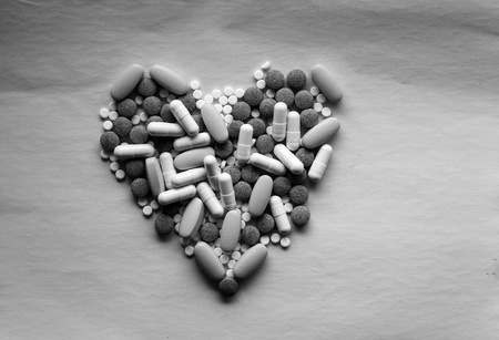 White, pink and green pills laid out in  shape of  heart on  pink background. multi-colored drugs. concept - heart disease, heart disorders and drugs, cardiology.