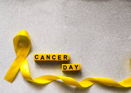 golden ribbon and words made up of childrens plastic beeches. concept - a symbol of childhood cancer, pediatric oncology. Stock Photo