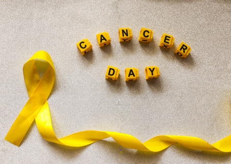golden ribbon and words made up of children's plastic beeches. concept - a symbol of childhood cancer, pediatric oncology.