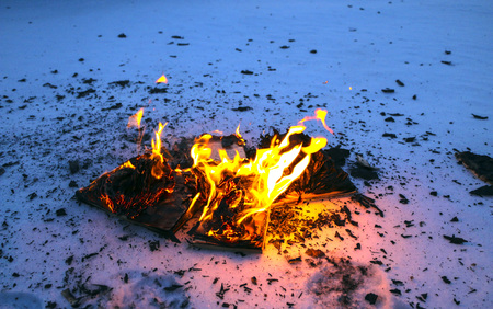 burning book in the snow. pages with the text in the open book burn with a bright flame.
