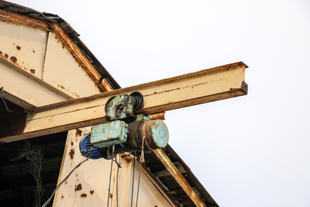 an old girder crane with a large iron hook lifts a heavy load on the slings