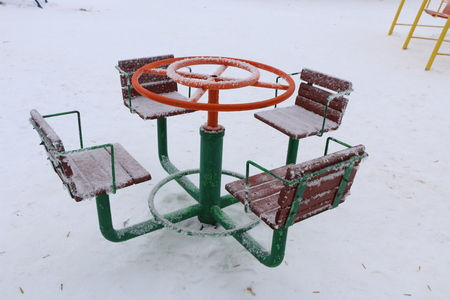 playground with swings, benches, slide and sports units in the snow.