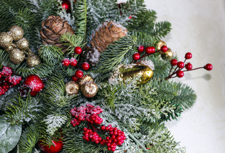 Christmas composition of pine branches, golden Christmas balls, red berries and artificial snow. Standard-Bild