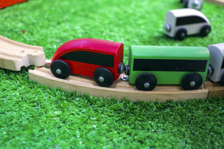 Children's wooden train with cars, railway and wooden trees on artificial plastic green grass. 免版税图像
