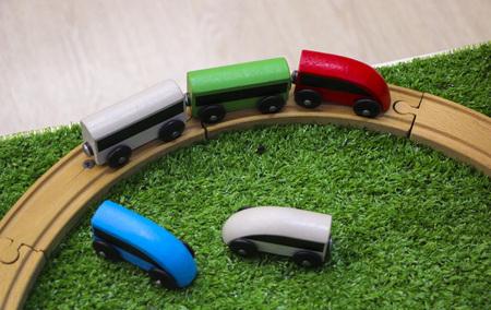 Houten kindertrein met auto's, spoorwegen en houten bomen op groen kunstgras.